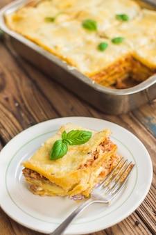 Lasagne fatte in casa pronte da mangiare in teglia di metallo servite con foglie di basilico
