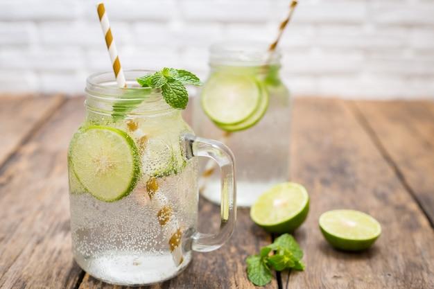 Bevanda limonata fatta in casa con calce fresca in vetro su legno vecchio