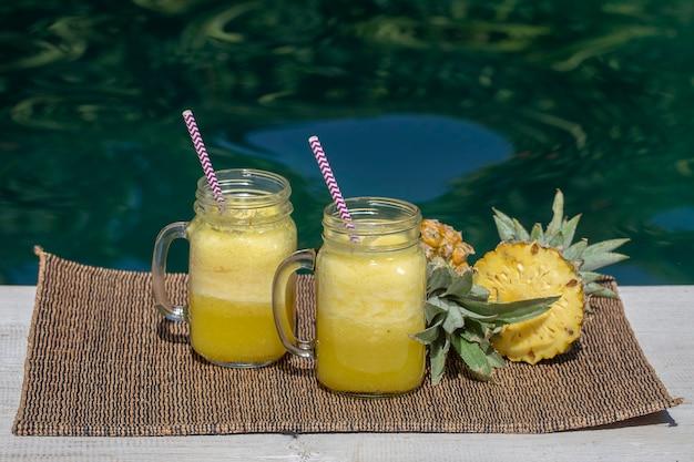 Frullato fatto in casa di mango e ananas fatto con latte di cocco in due tazze di vetro vicino alla piscina vicino isola bali indonesia bevanda rinfrescante di frutta tropicale il concetto di mangiare sano