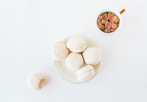 Marshmallow fatti in casa in un piatto e una tazza con tisana di fiori su sfondo bianco