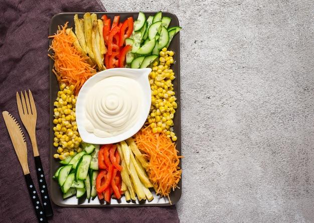 Salsa maionese fatta in casa e set di verdure colorate. capra russa dell'insalata nel giardino. vista dall'alto con copia spazio.