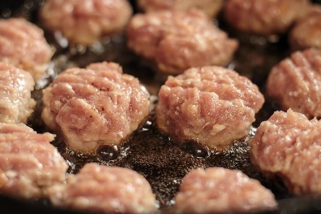 Cotolette di carne fatte in casa che cucinano in olio su una padella, piccola profondità di fuoco. porzione di carne affettata arrostita in padella.