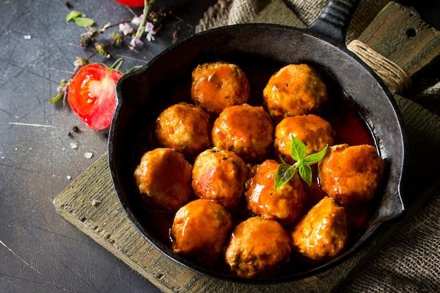 Polpette fatte in casa con spezie e salsa di pomodoro in padella sul tavolo di pietra scura