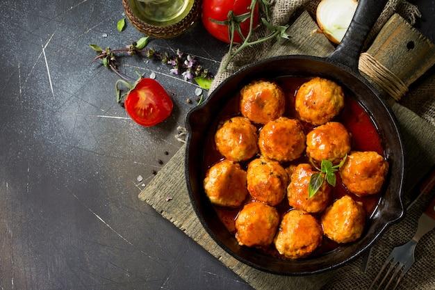 Polpette fatte in casa con spezie e salsa di pomodoro in una padella vista dall'alto piatta sullo sfondo