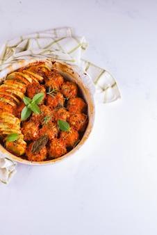 Polpette fatte in casa con salsa di pomodoro in un piatto bianco al forno con erbe su superficie bianca di marmo