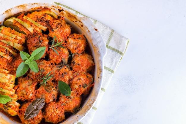 Polpette fatte in casa con salsa di pomodoro in un piatto bianco cotte al forno con erbe su marmo bianco