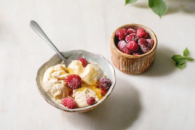 Gelato alla vaniglia al caramello fuso fatto in casa con sciroppo e lamponi congelati in una ciotola di ceramica in piedi sul tavolo di marmo bianco