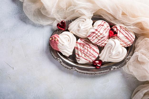 Meringhe fatte in casa a forma di cuore sulla vecchia piastra metallica per il giorno di san valentino, vista dall'alto, copia dello spazio