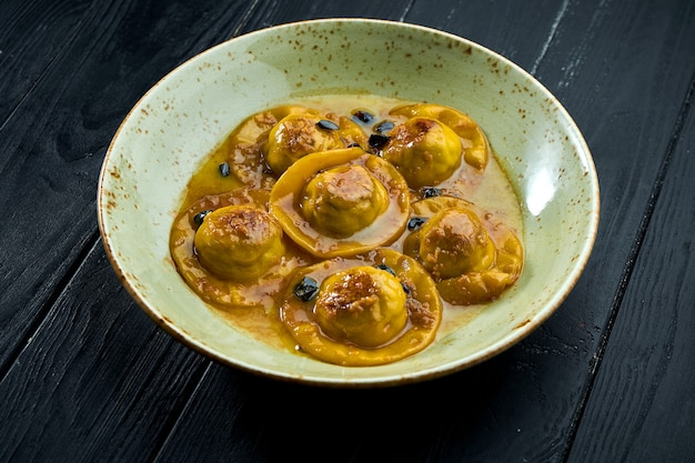 Ravioli fatti in casa e da leccarsi i baffi con petto d'anatra e mirtilli rossi, serviti con salsa in un piatto blu su fondo di legno scuro.