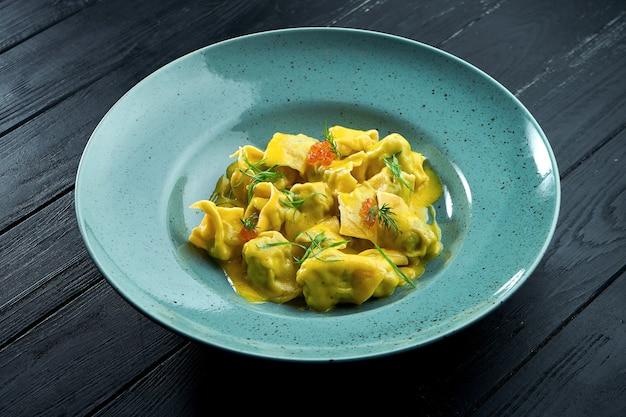 Ravioli fatti in casa e da leccarsi i baffi con salmone e caviale, serviti con salsa alla crema in un piatto blu su fondo di legno scuro.