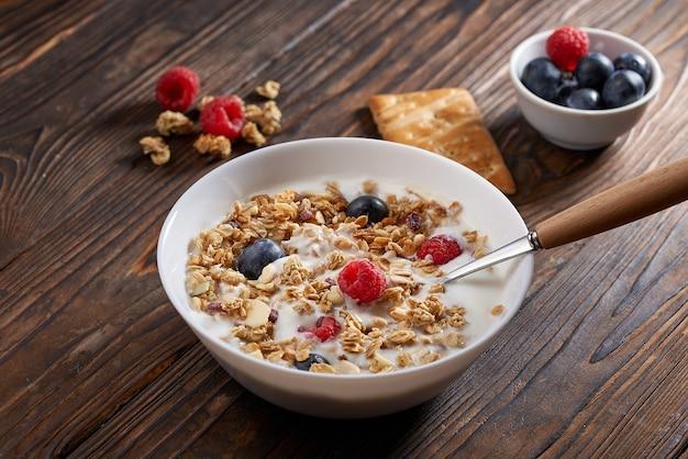 Prima colazione fatta in casa di muesli muesli con yogurt bianco, mirtilli e lamponi su tavola in legno rustico