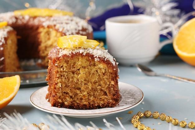 Muffin fatto in casa con arance cosparse di scaglie di cocco su uno sfondo azzurro e una tazza di caffè, un pezzo di muffin in primo piano, primo piano