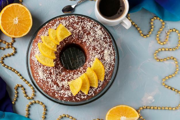 Muffin fatto in casa con arance con un buco al centro, cosparso di scaglie di cocco su uno sfondo azzurro e una tazza di caffè, spazio copia, vista dall'alto