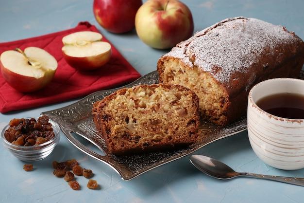 Muffin fatti in casa con semola, mele e uvetta su un vassoio di metallo su uno sfondo azzurro e una tazza di caffè, primo piano