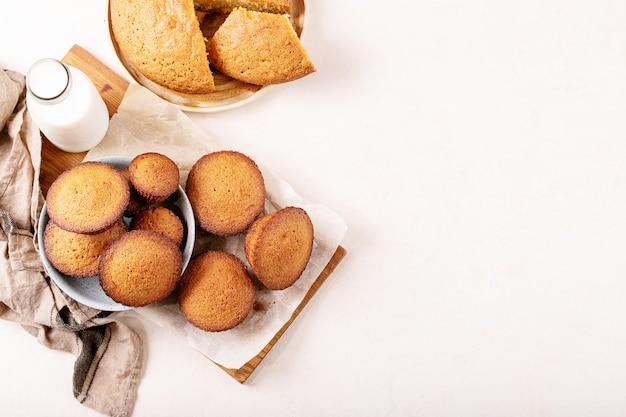 Muffin fatti in casa serviti con latte in una bottiglia su priorità bassa bianca di struttura. vista dall'alto, distesa piatta. copia spazio