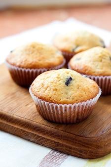 Muffin casalinghi con i mirtilli su un bordo di legno
