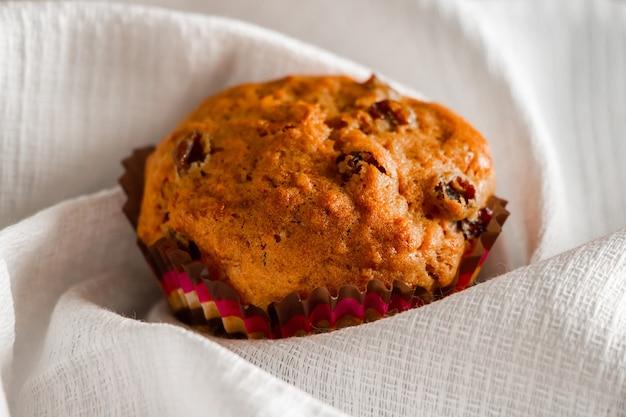 Muffin fatti in casa con uvetta su uno sfondo di legno. cupcake in uno stampo di carta su un tovagliolo bianco.