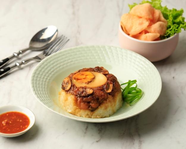 Nasi tim ayam jamur fatto in casa (riso al vapore con pollo e funghi) con salsa di soia e uova sode. servito con cracker e sambal. vista dall'alto con copia spazio per il testo