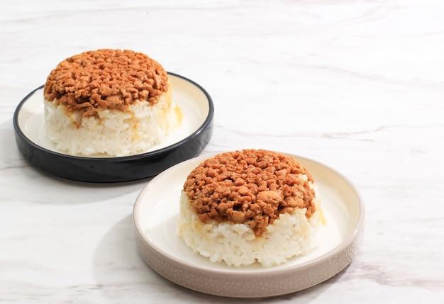 Nasi tim ayam fatto in casa, riso al vapore con salsa di soia di pollo a dadini. comfort food indonesiano per la colazione. servito su piatto in ceramica con copia spazio per il testo