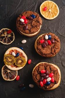 Panino casalingo dei biscotti del cioccolato dell'avena con gli agrumi secchi e i fagioli di gelatina succosi sulla superficie strutturata del nero scuro, vista superiore