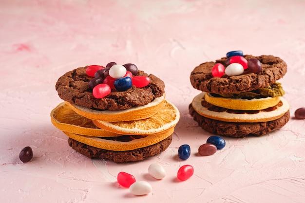 Panino casalingo dei biscotti del cioccolato dell'avena con gli agrumi secchi e i fagioli di gelatina succosi su superficie rosa strutturata, vista di angolo