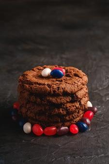 Pila casalinga dei biscotti del cioccolato dell'avena con cereale con i fagioli di gelatina succosi sulla superficie strutturata del nero scuro, vista di angolo