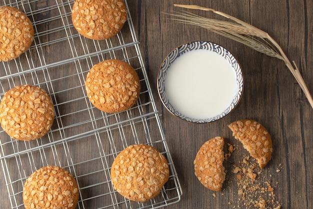Biscotti di farina d'avena fatti in casa con semi e ciotola di latte fresco su una superficie di legno