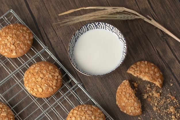 Biscotti di farina d'avena fatti in casa con semi e ciotola di latte fresco sulla tavola di legno