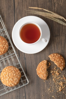 Biscotti di farina d'avena fatti in casa con semi e tazza di tè su una superficie di legno