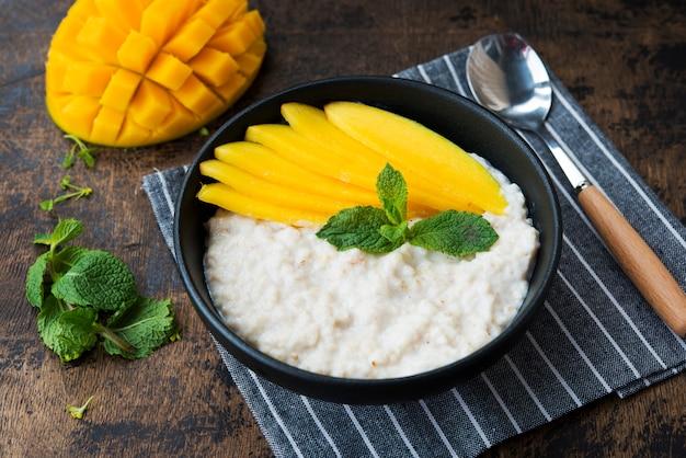 Ciotola di farina d'avena fatta in casa con latte e fette di mango fresche