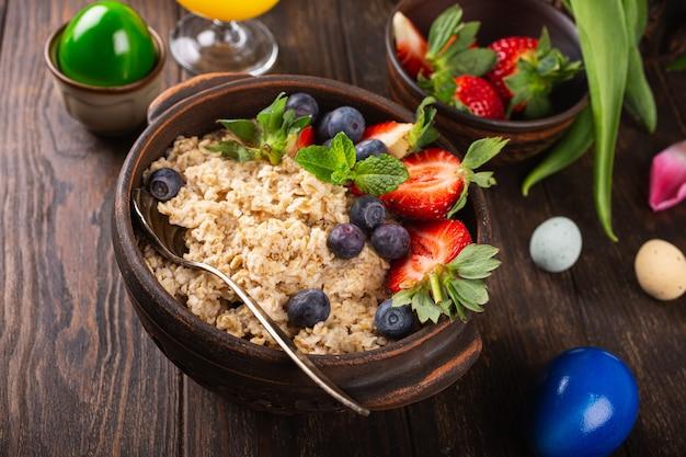 Muesli o muesli di farina d'avena fatti in casa con frutti di bosco freschi per una sana colazione mattutina di pasqua, fuoco selettivo. superficie di cibo sano, copia dello spazio