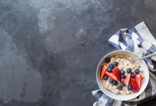 Farina d'avena fatta in casa con mirtilli e fragole in una ciotola su cemento grigio