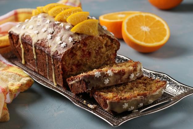 Torta all'arancia fatta in casa con mirtilli rossi ricoperta di glassa e fette di arance su vassoio di metallo su sfondo azzurro. avvicinamento. formato orizzontale