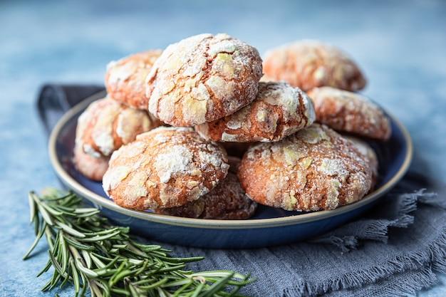 Biscotti di pasta frolla all'arancia fatti in casa con zucchero a velo, rosmarino e arance rosse siciliane su superficie di cemento blu