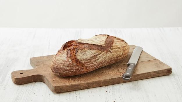 Pane biologico fatto in casa su un tagliere con un coltello isolato su uno sfondo bianco