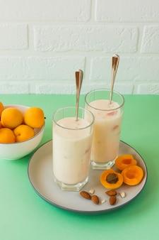 Frullato biologico fatto in casa di yogurt e albicocca. in palla alta, su un tavolo, con albicocche.