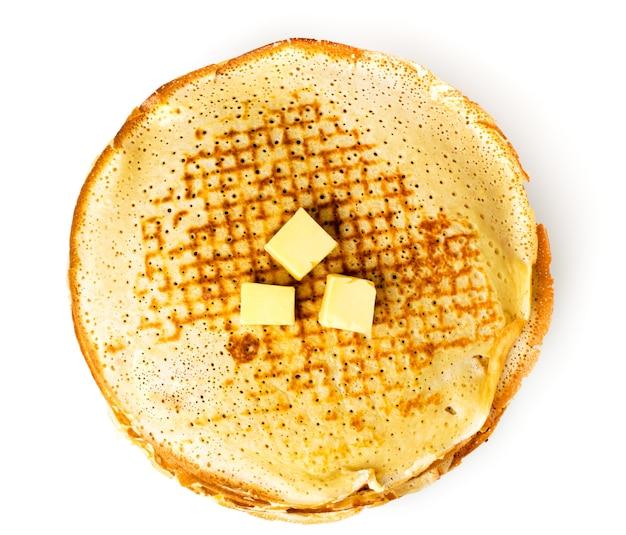 Frittelle fatte in casa con burro su una superficie bianca, isolata.