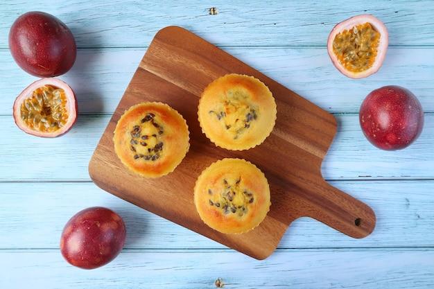 Muffin fatti in casa al frutto della passione su breadboard con frutti della passione freschi sulla tavola di legno