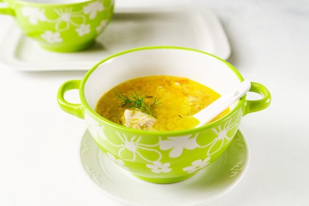 La zuppa di pollo fatta in casa è servita in una ciotola verde chiaro su un vassoio bianco