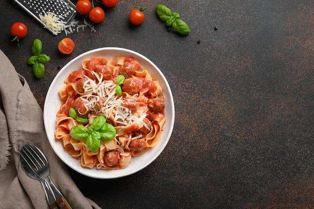 Fettuccine di pasta fatta in casa con polpette di parmigiano pomodori basilico vista dall'alto