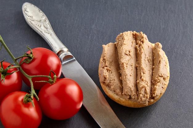 Panino di patè fatto in casa sulla tavola di pietra nera con pomodorini e coltello da cucina