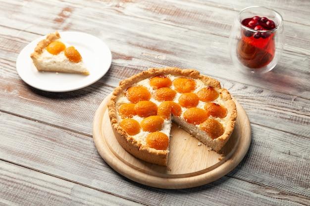 Cheesecake alla pesca fatta in casa, tazza di tè ai frutti di bosco, pezzo di torta vicino alla piastra