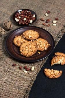 Biscotti fatti in casa di arachidi su un piatto marrone con arachidi crude in superficie. cibo in stile rustico