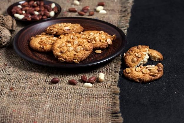 Biscotti fatti in casa di arachidi su un piatto marrone con arachidi crude