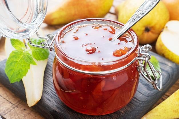 Marmellata di pere fatta in casa in un barattolo e pere fresche su uno sfondo di legno.