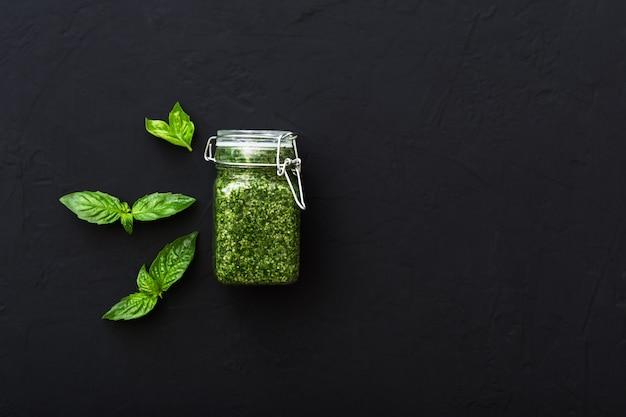 Pesto fatto in casa e basilico verde su cemento scuro