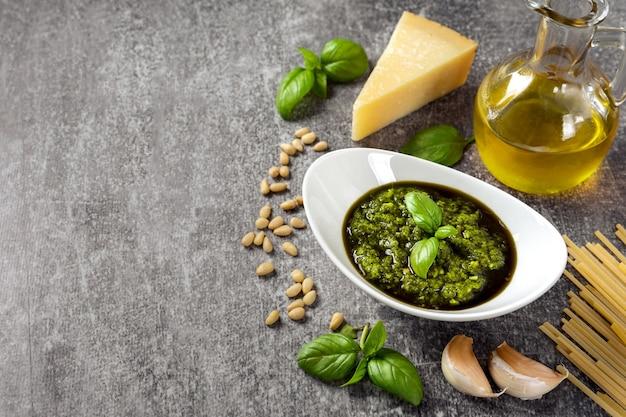 Pesto fatto in casa con ingredienti. salsa al pesto in una ciotola bianca con basilico, olio d'oliva, pinoli e parmigiano su sfondo grigio cemento con copia spazio per il testo.