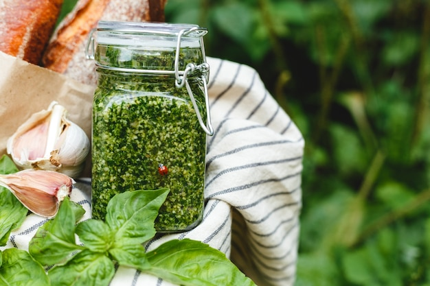Salsa di pesto fatto in casa in un barattolo di vetro con basilico, aglio, pane all'aperto nel cestino da picnic
