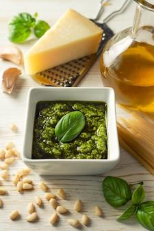 Salsa al pesto fatta in casa con ingredienti. salsa il pesto in ciotola bianca con basilico, olio d'oliva, pinoli e parmigiano su fondo di legno bianco con lo spazio della copia per testo.