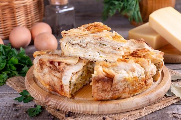 Torta fatta in casa con formaggio ed erbe aromatiche sul tavolo